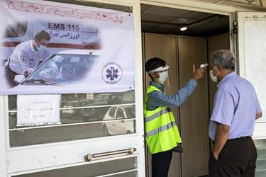 یکی از نیرو های اورژانس مشغول تب سنجی از مراجعین در اولین روز طرح ضربتی واکسیناسیون کرونا توسط نیروهای اورژانس است.
