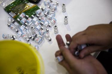 یکی از نیروهای اورژانس مشغول شمارش ظروف خالی واکسن های تزریق شده است.