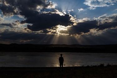 نمایی از غروب تالاب قوری گول در حالیکه جوانی برای تماشای آن ایستاده، دیده میشود.