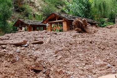 انبوهی از کل و لای همراه با سنگ و درختان که موجب تخریب الاچیق شد