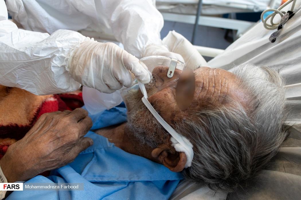 پرستار بخش حاد یک ماسک اکسیژن بیمار کرونایی را تنظیم می کند. /  بیمارستان حضرت علی اصغر(ع) شیراز