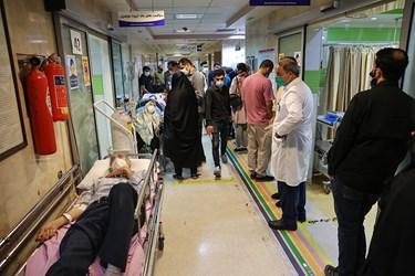 بیمارستان بقیه الله(عج) جهت رفاه حال بیماران بدحال از تخت به صورت موقت در راهروی درمانگاه بخش خاکستری استفاده نموده است. همچنین بیماران مشکوک به کرونا در صف سی تی اسکن ریه ایستاده اند