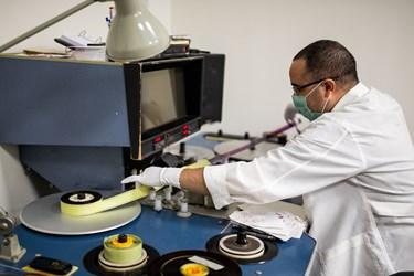 یکی از متخصصان در حال جای گذاری نگاتیو به یکی از دستگاهها در فیلمخانه ملی ایران