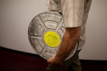 انتقال یکی از قوطیهای نگاتیو جهت بازبینی و شرح نویسی فیلم (۳۵میلیمتری) با دستگاه بازبینی فیلم (موویلا) توسط یکی از متخصصان در فیلمخانه ملی ایران