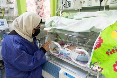 مادر قل یکم (  قل A  ) دختر را در بخش مراقبت های ویژه نوزادان (  NICU 1 ) از پشت دستگاه انکوباتور به نوزادش نگاه می کند./ بیمارستان حضرت زینب(س) شیراز