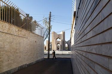 مردی در حال  عبور از مقابل کوچهای مشرف به بنای مقبرةالشعرا در شهر تبریز است.