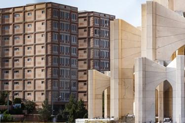 نمایی از محوطه مقبرةالشعرا در کنار معماری مدرن برجهای مسکونی دیده میشود.