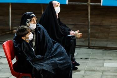 مادربزرگی روی نوه خود را برای گرم کردن و حفاظت از سرمای هوا با چادر پوشانده است. آنها در همایش ملی روز شعر و ادب فارسی و بزرگداشت استاد شهریار شرکت کردهاند.