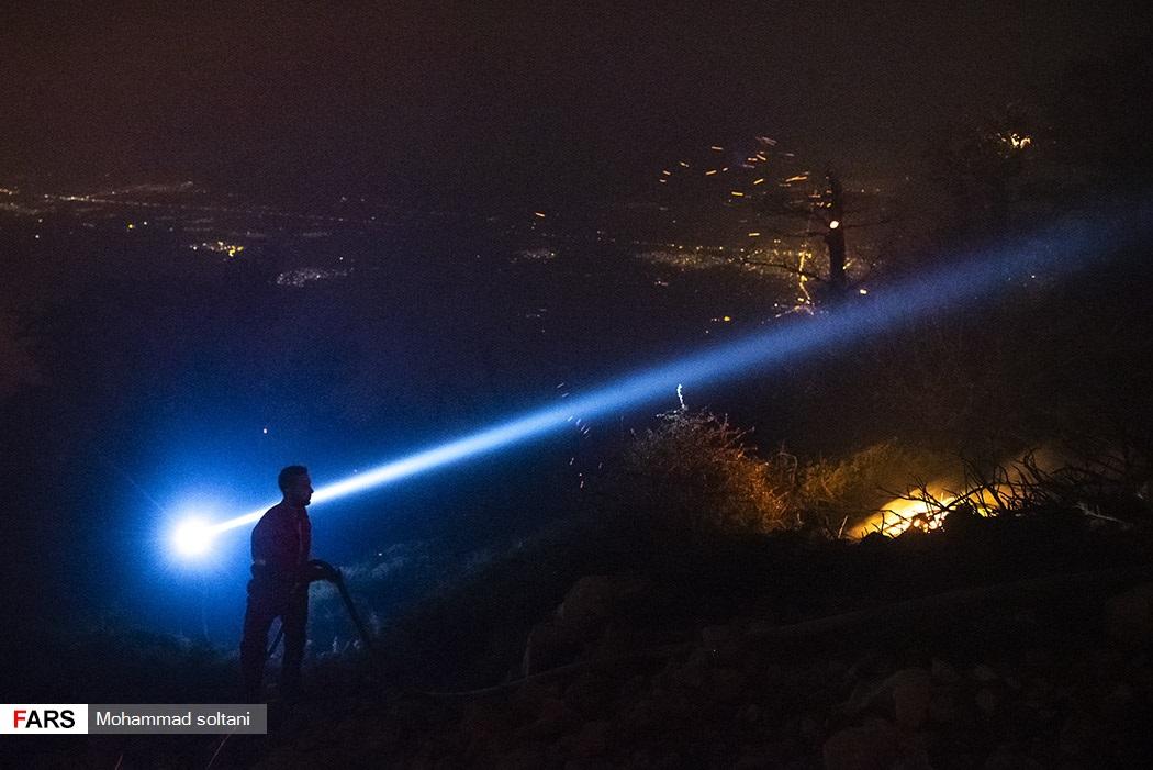 تلاش نیرو های محیط زیست برای خاموش کردن آتش در تاریکی شب