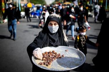 دختری در ابتدای مسیر راهپیمایی جاماندگان با سینی حاوی خرما، ارده در حال پذیرایی از مردم است