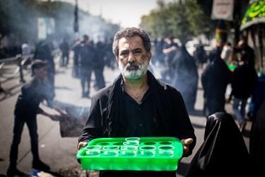 خادمی در مسیر راهپیمایی جاماندگان در حال پذیرایی  از جاماندگان حسینی(ع) است