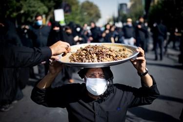 خادمی در مسیر راهپیمایی جاماندگان با سینی حاوی خرما، ارده در حال پذیرایی از مردم است