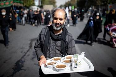 یک خادم در مسیر راهپیمایی جاماندگان با پخش کردن نذری در میان  جاماندگان در حال خدمت رسانی به مردم است