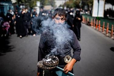 خادمی در مسیر راهپیمایی جاماندگان در حال دود کردن اسپند برای جاماندگان حسینی(ع) است
