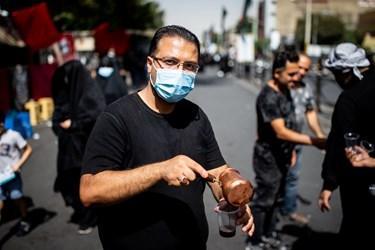 یک خادم در مسیر راهپیمایی جاماندگان در حال پذیرایی با قهوه از جاماندگان حسینی(ع)به  است