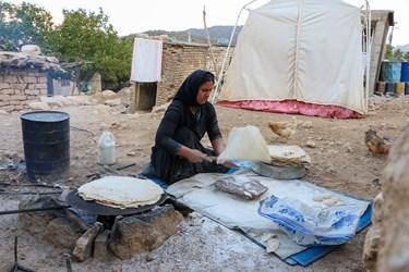 پخت نان توسط همسر خانواده در کنار چادر های امدادی